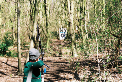 archer shooting target through trees